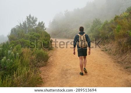 Rear view of a young man walking on a nature trail away from the camera with the natural surrounds disappearing into morning mist - stock photo