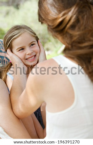 Rear view of a young mother holding her young daughter face in her hands while sitting together in a hammock in a holiday home garden during a summer vacation. Family activities lifestyle outdoors. - stock photo