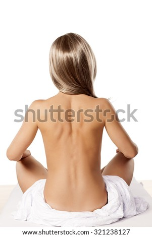 rear view of a young naked woman sitting on a bed