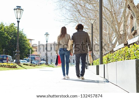 Rear view of a young tourist couple on vacation in a destination city carrying shopping bags and holding hands. - stock photo