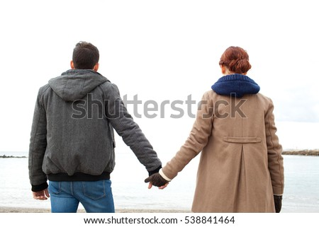 Rear view of a young tourist couple standing on a winter beach destination, holding hands contemplating the sea on a seasonal holiday, nature outdoors. Recreation travel lifestyle, coastal exterior.