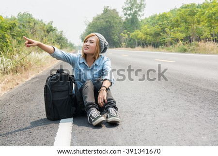 Rear view of a young woman hitchhiking carrying backpack sitting on the road  - stock photo