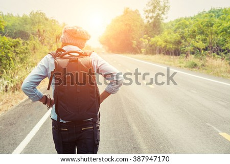 Rear view of a young woman hitchhiking on countryside road walking on the road - stock photo