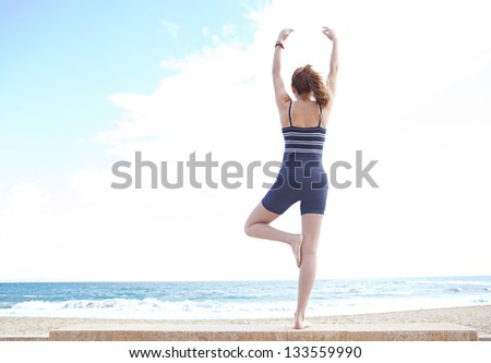 Rear view of a young woman in a yoga tree position on a golden beach with her arms open against a blue sky.