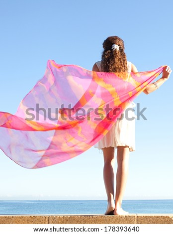 Rear view of a young woman rising a bright and colorful floating sarong fabric up with her arms against a bright blue sky and sea on a holiday beach, outdoors. Travel and lifestyle. - stock photo