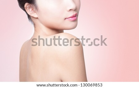 Rear view of a young woman shoulder isolated on pink background, asian beauty