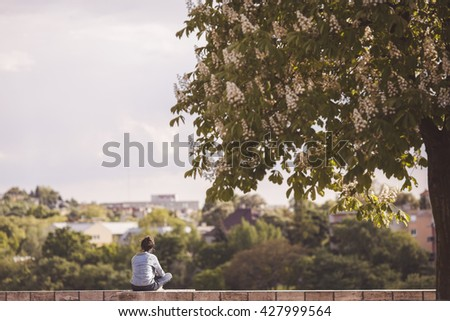 Rear view of a young woman sitting on a brick wall peacefully under a tree. selective focus - stock photo