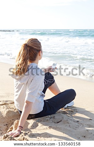 Rear view of a young woman sitting on a golden beach shore, holding an mp4 player in her hand while listening to music with ear phones. - stock photo