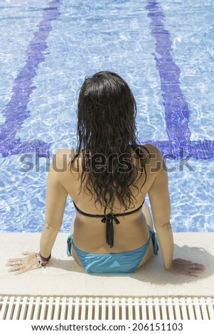 rear view of a young woman sitting on the edge of the pool