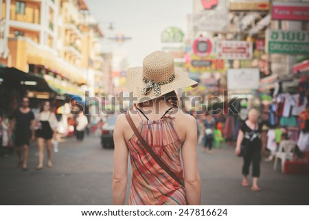 Rear view of a young woman walking the famous backpacker street Khao San in Bangkok, Thailand - stock photo