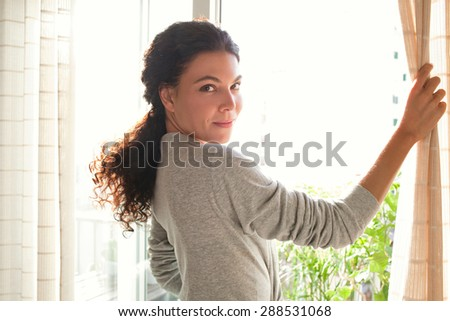 Rear view of a young woman wearing a robe and holding the curtains open to look out of a large light window at home, turning to look and smile at camera, interior. Aspirational lifestyle, indoors. - stock photo