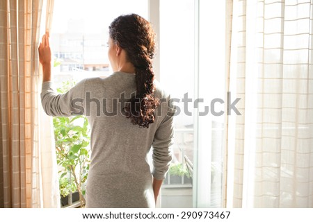 Rear view of a young woman wearing a robe and holding the curtains open to look out of a large light window at home, interior. Positive and aspirational lifestyle. Woman looking out a window, indoors.