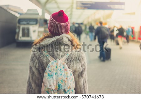 Rear view of a young woman with a winter hat standing in a station