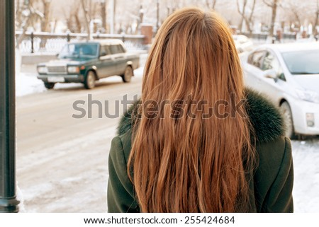 Rear view of a young woman with blond hair in the street. - stock photo