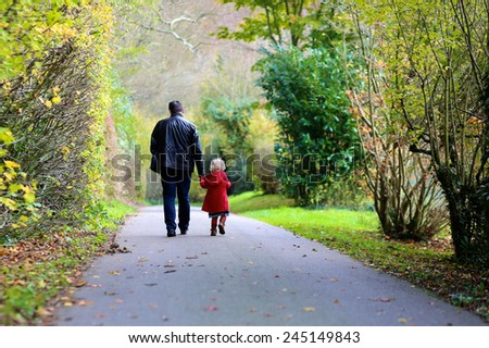 Rear view of active father and little child, blonde toddler girl in beautiful red coat walking hand in hand in autumn or spring park