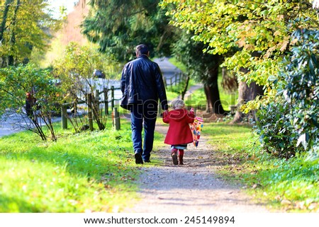 Rear view of active father and little child, blonde toddler girl in beautiful red coat with colorful umbrella walking hand in hand in autumn or spring park on a sunny day - stock photo