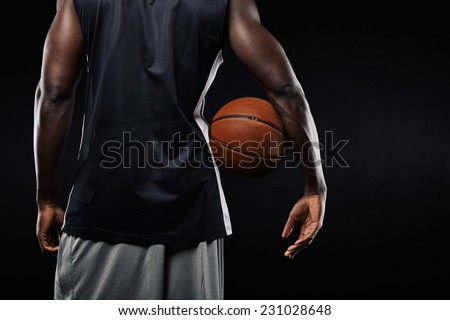 Rear view of african basketball player with a ball in his arm against black background with copyspace - stock photo