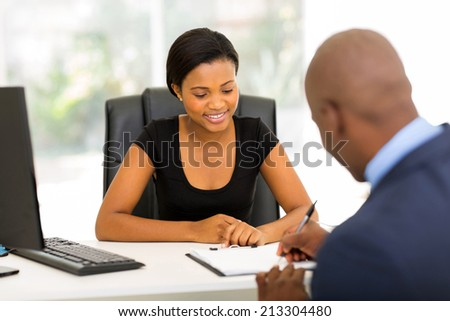 rear view of african businessman signing contract in office - stock photo