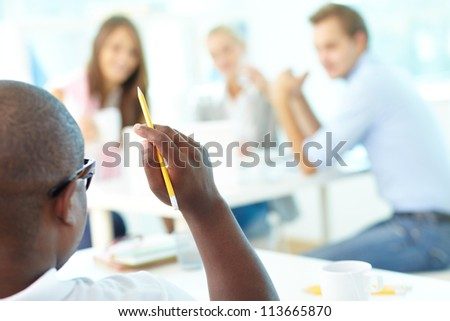 Rear view of African guy holding pencil with group of students looking at him
