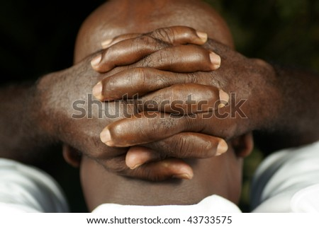 rear view of afro man with fingers clasped behind his head - stock photo