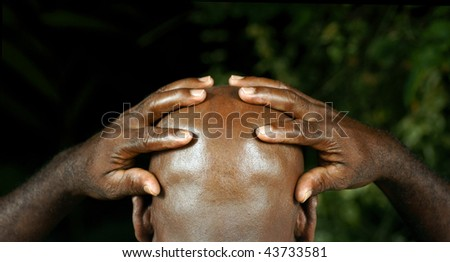 rear view of afro man with hands with fingers opened holding his head - stock photo
