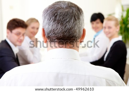 Rear view of aged businessman making report to partners at conference - stock photo