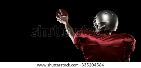 Rear view of American football player in red jersey holding ball against black