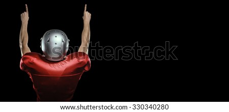 Rear view of American football player with arms raised against black - stock photo