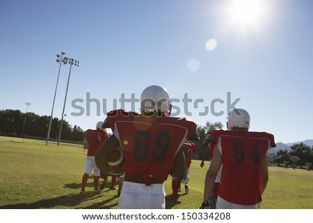 Rear view of American football team on field - stock photo