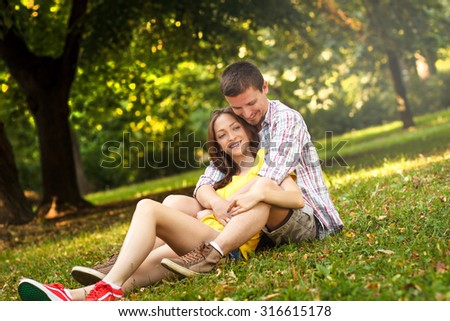 Rear view of an affectionate young couple sitting in park - stock photo