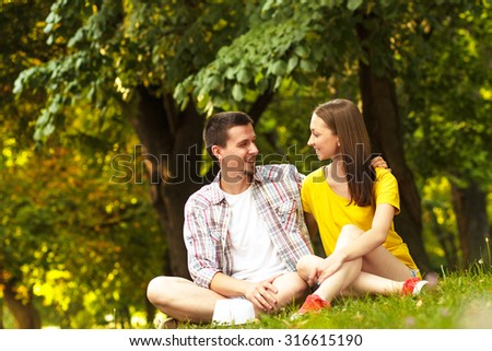 Rear view of an affectionate young couple sitting in park