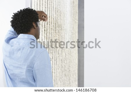 Rear view of an African American businessman leaning against office wall - stock photo