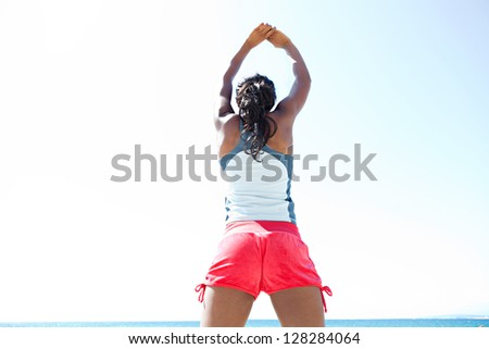 "Rear view of an ""african american"" woman stretching her arms and back while standing against a deep blue sky, exercising on a sunny day. - stock photo"