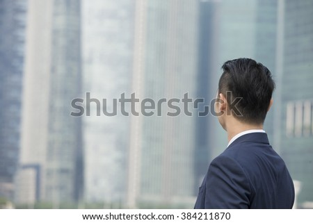 Rear view of an Asian businessman looking away. Chinese business man standing outdoors. - stock photo