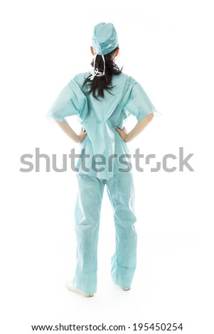Rear view of an Asian female surgeon standing with hands on hip - stock photo