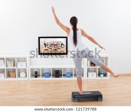 Rear view of an athletic barefoot young woman doing home exercises while watching program on television - stock photo