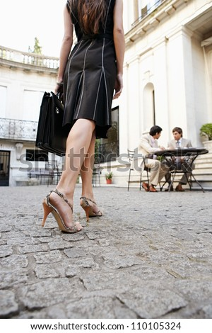 Rear view of an attractive businesswoman arriving at a meeting with colleagues at a coffee shop in a classic colonial building, outdoors. - stock photo