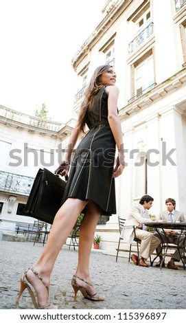 Rear view of an attractive elegant businesswoman walking to a business meeting in a luxury coffee shop terrace.
