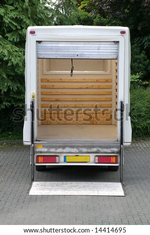 Rear view of an empty white box van with it's tail lift lowered. - stock photo
