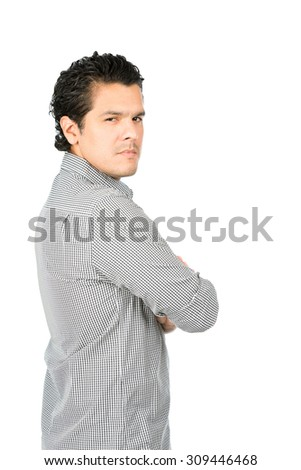 Rear view of angry, disappointed latino man wearing casual clothes arms crossed looking behind at camera over his shoulder showing judgmental, critical, unhappy, displeased attitude. Vertical half - stock photo