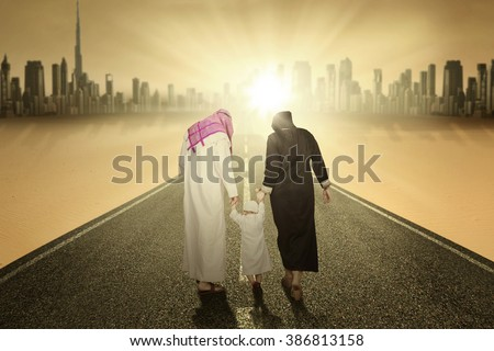 Rear view of arabic family walking on the highway while holding hands - stock photo