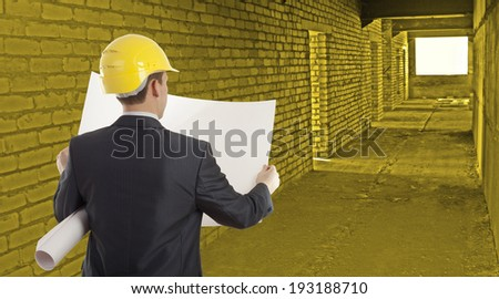 Rear view of architect looking comparing paper plan housing project with building wearing yellow helmet  Back view businessman in perspective long corridor with door and window background - stock photo