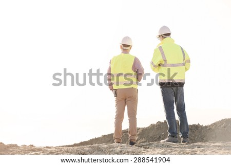 Rear view of architects standing at construction site against clear sky - stock photo