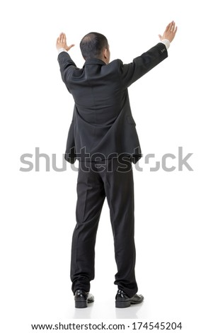 Rear view of Asian business man raising hand to put something over his head, full length isolated on white. - stock photo
