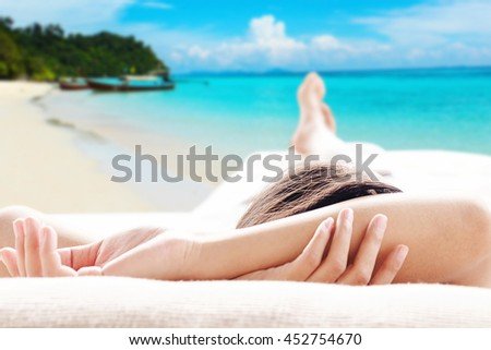 Rear view of asian woman relaxing on a sofa at the beach and looking outside beautiful sea and island background view . Relaxing concept.   - stock photo