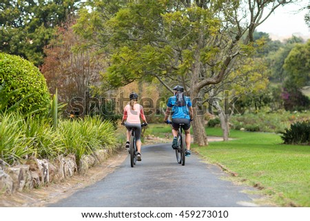 Rear view of athletic couple cycling on the road