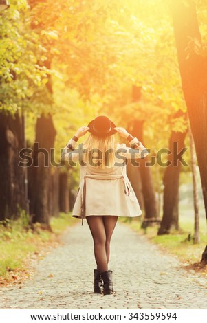 Rear view of attractive young blonde woman in autumn in park wearing beige trench coat, black boots and black fedora hat. Vibrant colors, retouched, filter applied. - stock photo