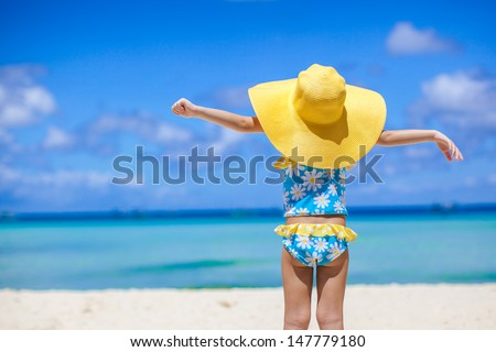 Rear view of baby girl in big hat looking at the sea on white sand beach - stock photo