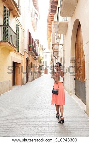 Rear view of beautiful african american tourist woman visiting old town street, turning smiling looking at camera, destination holiday, outdoors. Travel experience lifestyle, black female, exterior.