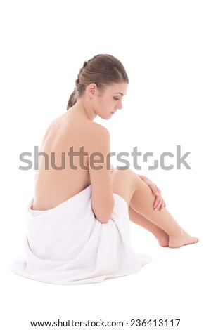 rear view of beautiful sexy woman wrapped in towel sitting isolated on white background